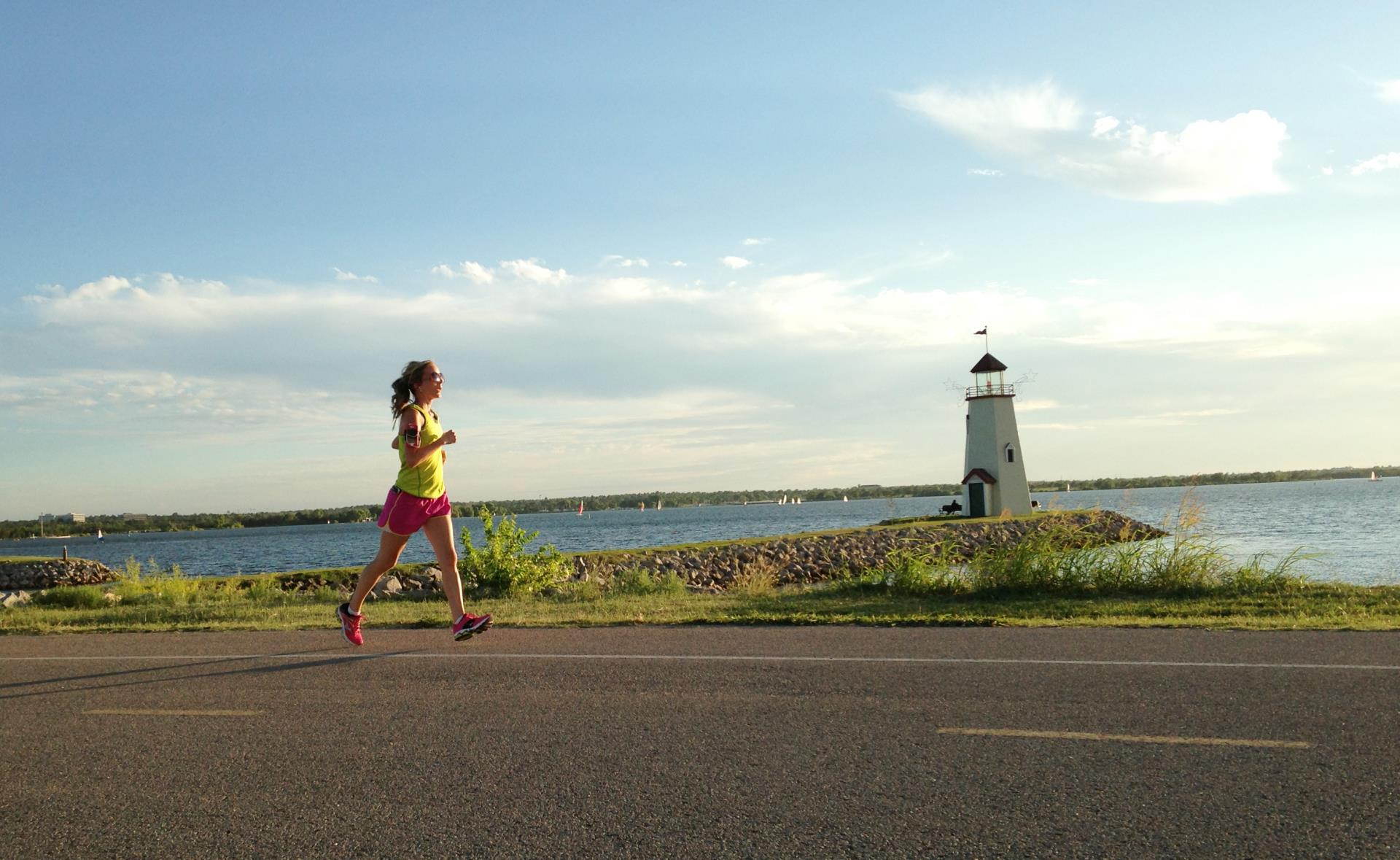 A runner enjoys a lighthouse view on the Burt Cooper Trails