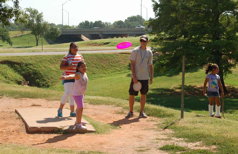 Young players tee off at the Will Rogers Disc Golf Course