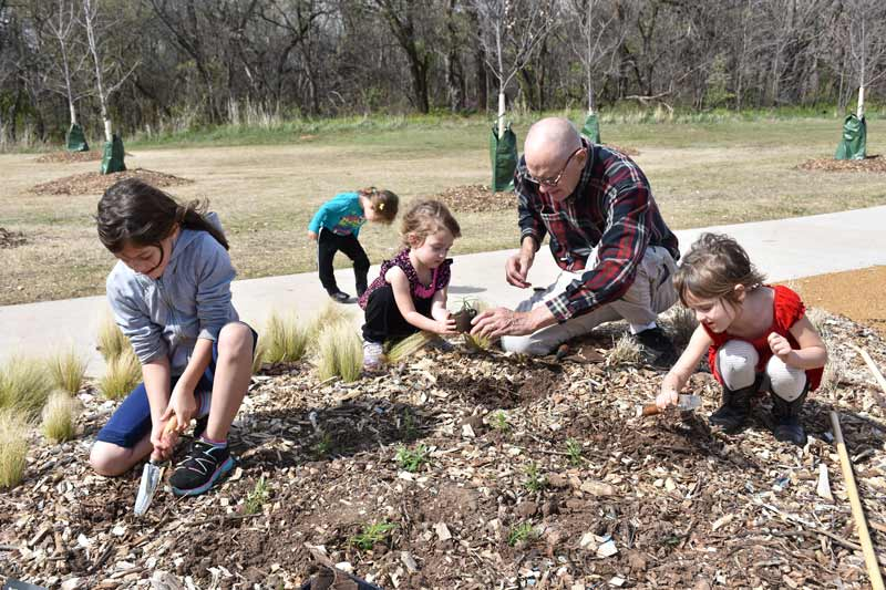 A grandfather and his granddaughters plant Milkweed at Bluff Creek Park